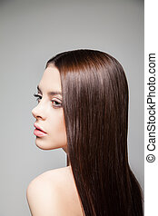 Young brunette looking over shoulder - Side view of young...