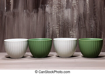 Green and white bowls on brown wooden background