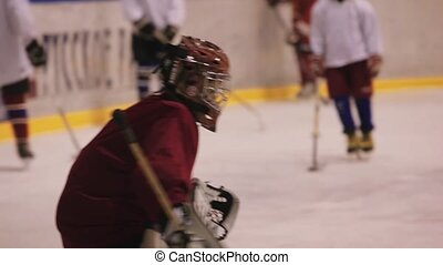 Coaching children's hockey team. Junior Goalkeeper protects...