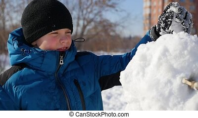 child making a snowman in the Playground
