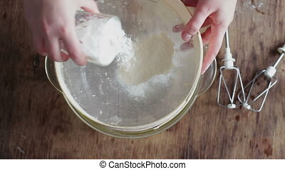 Top view of woman sieving flour the plate - Female hand pour...