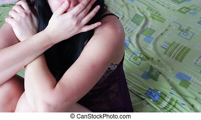 Frightened crying woman with a bruise half-dressed sitting on the bed domestic violence