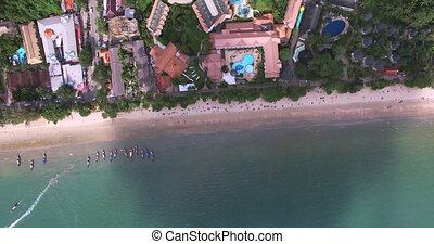 Aerial view flying over Thai island towards beautiful green...