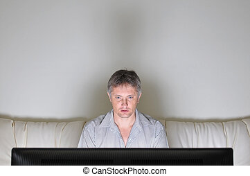 Watching television - Man alone staring at a television or...