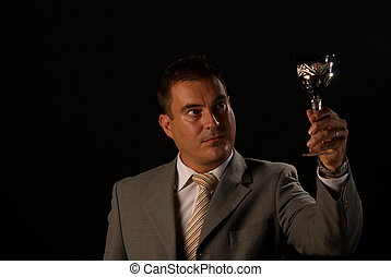 Connoisseur - Man holding up a crystal glass with white wine