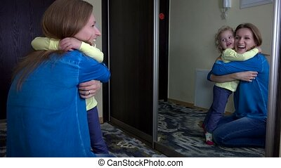 Loving woman hug her daughter girl near mirror and simper....