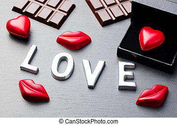Love word, heart and lips shaped chocolate candies with...