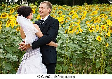 Groom looks in bride eyes standing behind a field of...