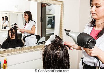 Hairdresser drying dark female hair using professional hairdryer