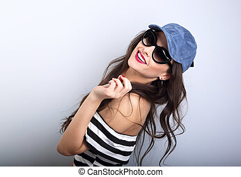 Enjoyment young woman in sunglasses and blue baseball cap...