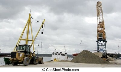 Ships dredge unloads sand on dock - The crane dredge of a...
