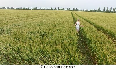 Woman with blonde hair in a blue dress walking in the field with wheat.