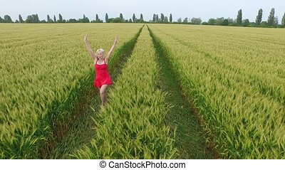 Woman with blonde hair in a red dress runsin the field with...
