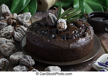 Whole chocolate cake on dark brown wooden table with coffee...