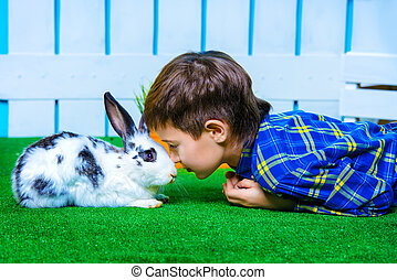 eyes to eyes - Happy child boy lying on a grass with Easter...