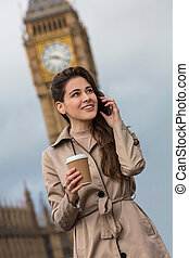 Woman Drinking Coffee Using Cell Phone, Big Ben, London, England