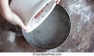 Top view of woman pours a chocolate dough in a baking tray -...