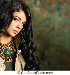 Beautiful fashion woman with curly hair and stage makeup on...