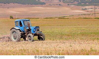 Plowing the field - Farm tractor plowed land Behind the...