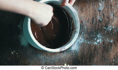 Top view stirring chocolate cookie dough with a spoon in a...