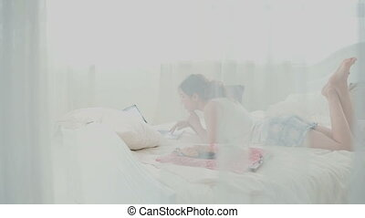 Young woman using wireless technology lying on a white bed...