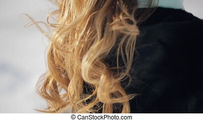 Blonde hair with curls shaking behind his back during gait...