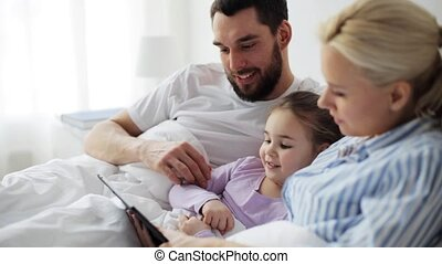 happy family with tablet pc in bed at home - people,...