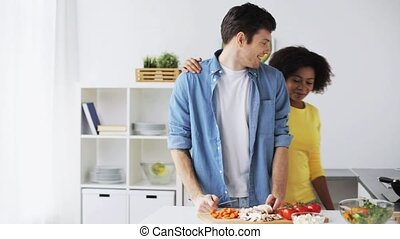happy couple cooking food at home kitchen - food, cooking,...