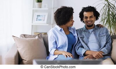 happy smiling couple watching tv at home