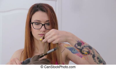 Professional hairdresser doing hairstyle for pretty teen...