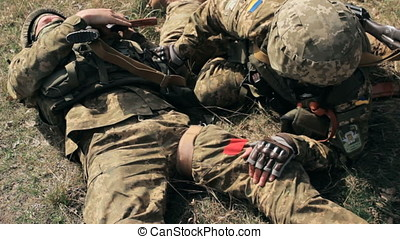 Military heals bandages his wounded friend under gunfire