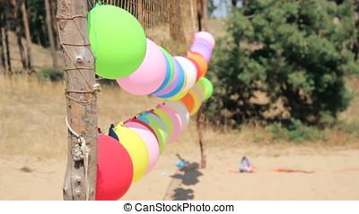 Girl shoot at balloons from gun at volleyball field