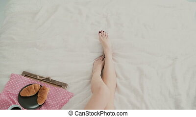 Close-up view of woman s foot. Young girl lying on the bed, having breakfast in living room.