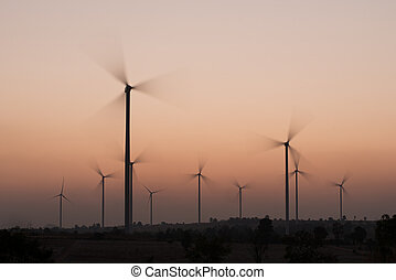 wind turbines spinning at sunset - silhouette of wind...