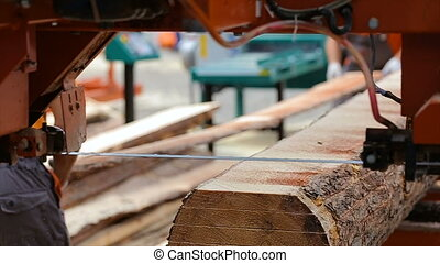two workers unload boards from the sawmills on the pile