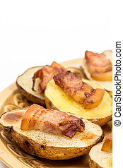 Baked potatoes with skin and bacon on it.