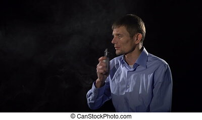 A man smokes an electronic cigarette and exhales steam
