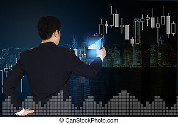 Double exposure of businessman using tablet with financial graph chart and building background.