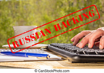 Man typing on a computer keyboard and RUSSIAN HACKING red...