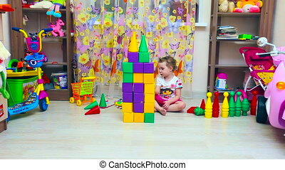 little girl builds pyramid of blocks