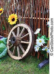 wooden wheel near fence