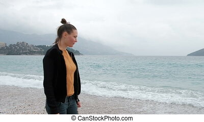 In overcast foggy morning woman walking on the beach with...