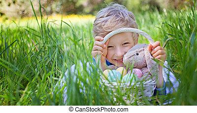 after easter egg hunt - smiling happy boy holding basket...