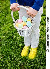 after easter egg hunt - little boy holding white basket with...