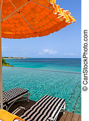 sunbeds by the pool - view at umbrella and two sunbeds by...