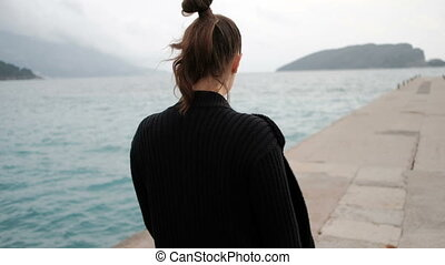 Shooting from back woman walking on sea shore looking into distance