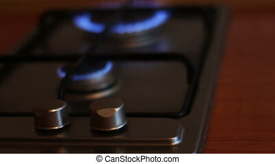 Burning blue flames of a gas stove close up view