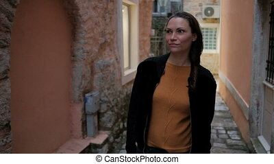 Young woman walking on the narrow old streets and touched...