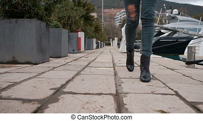 Close shot of woman with torn jeans legs in high heels walking