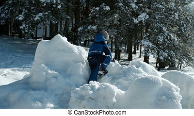 Boy in blue overalls climbs the hill in the winter...